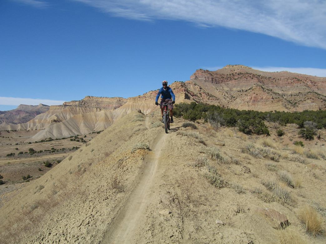 The desert stretches in the background of the singletrack at Fruita.