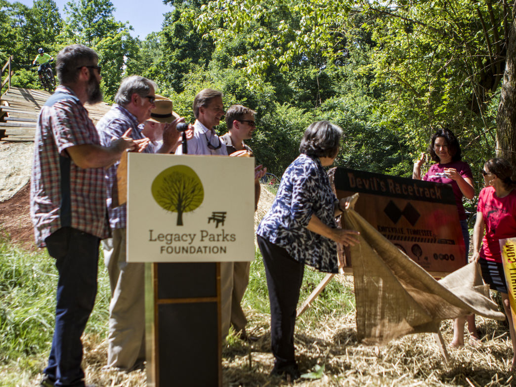 Knoxville Mayor Madeline Rogero, at center, and members of the Appalachian Mountain Bike Club unveil the Devil's Racretrack gravity course in south Knoxville.
