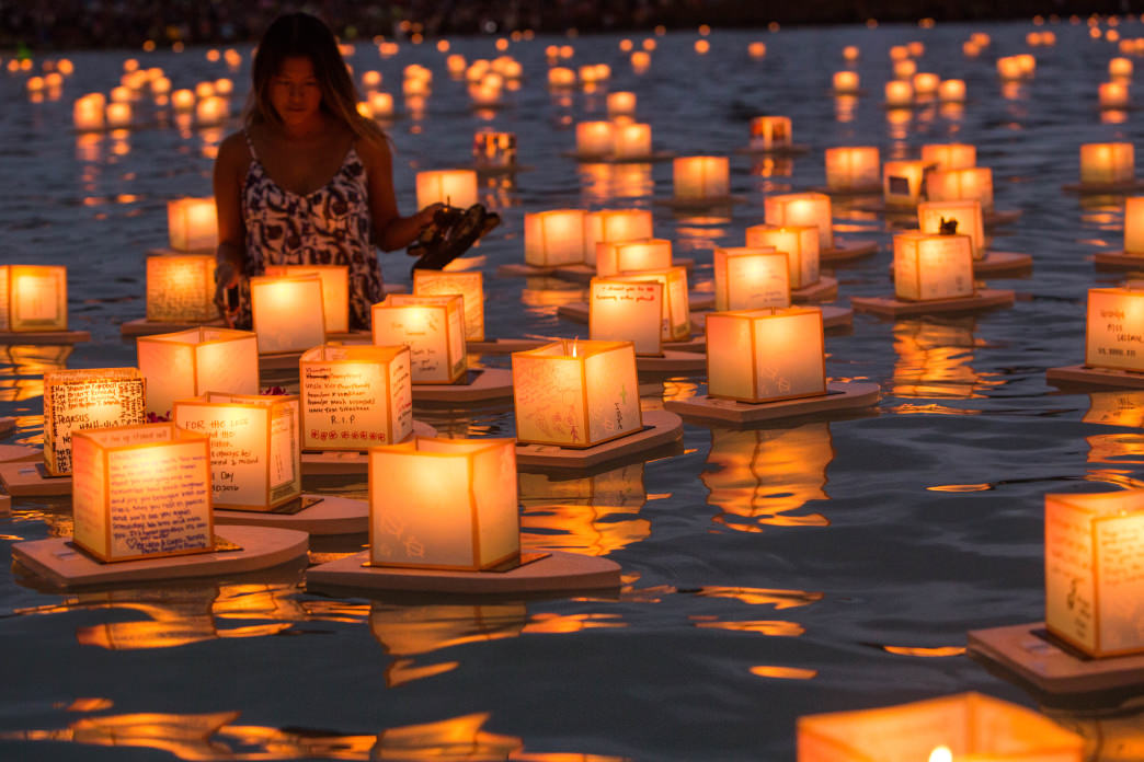 A woman reads the messages that have been sent out to the sea at the Hawaii Lantern Floating Ceremony.
