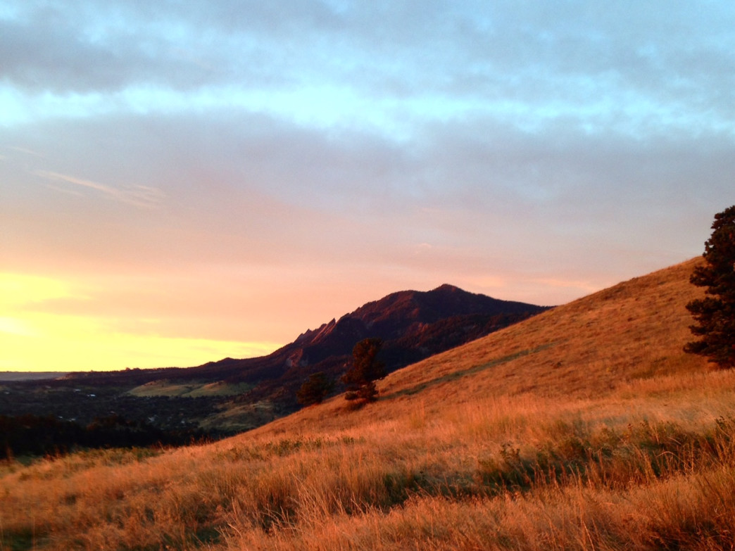 The sun rises over the grassy flank of Mount Sanitas