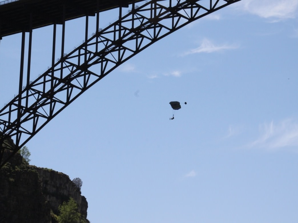 Base jumpers fly off the Perrine Bridge, entertaining paddlers on the Snake River below.