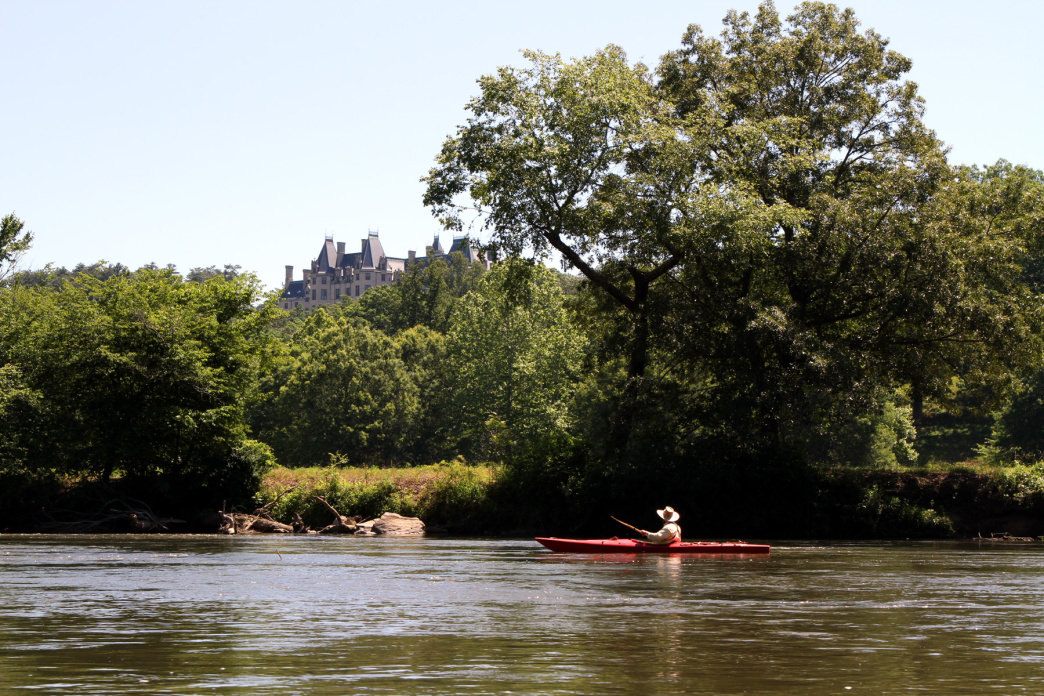 A kayaker on the French Broad River takes a peek at the Biltmore Estate.