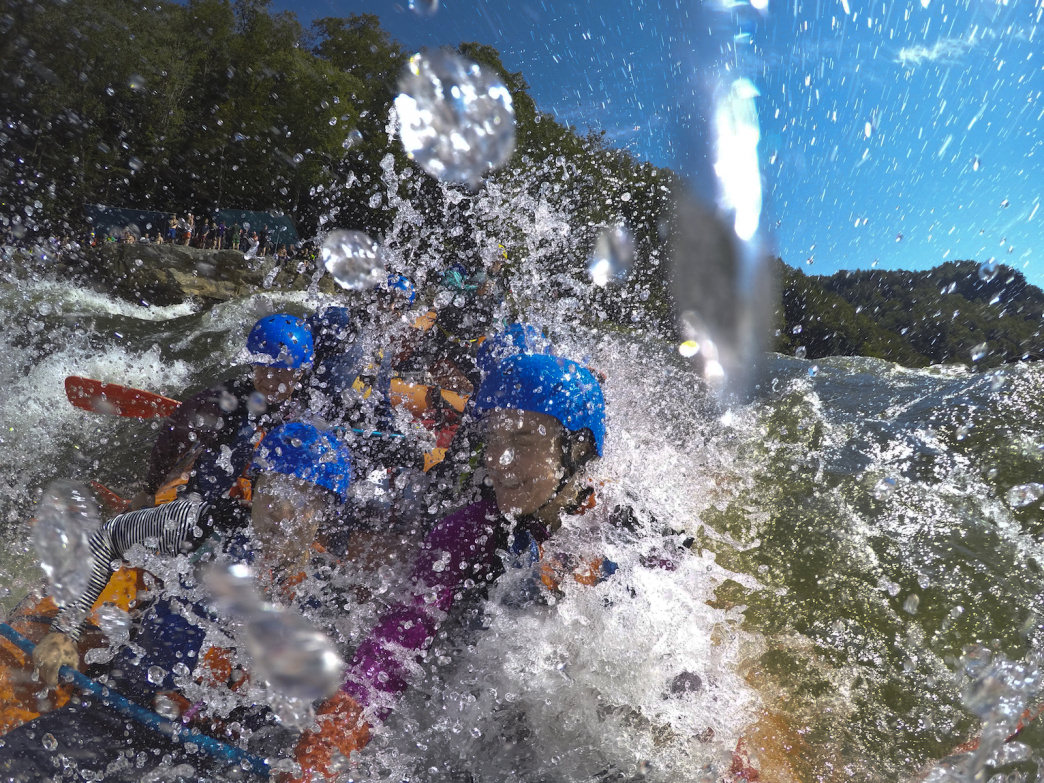 A commercial raft crew drops into the foam pile at the bottom of class-V Sweet's Falls as spectators line the banks.