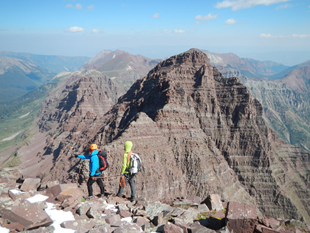 A team starts the traverse from the summit of Maroon Peak. North Maroon Peak is in the distance.