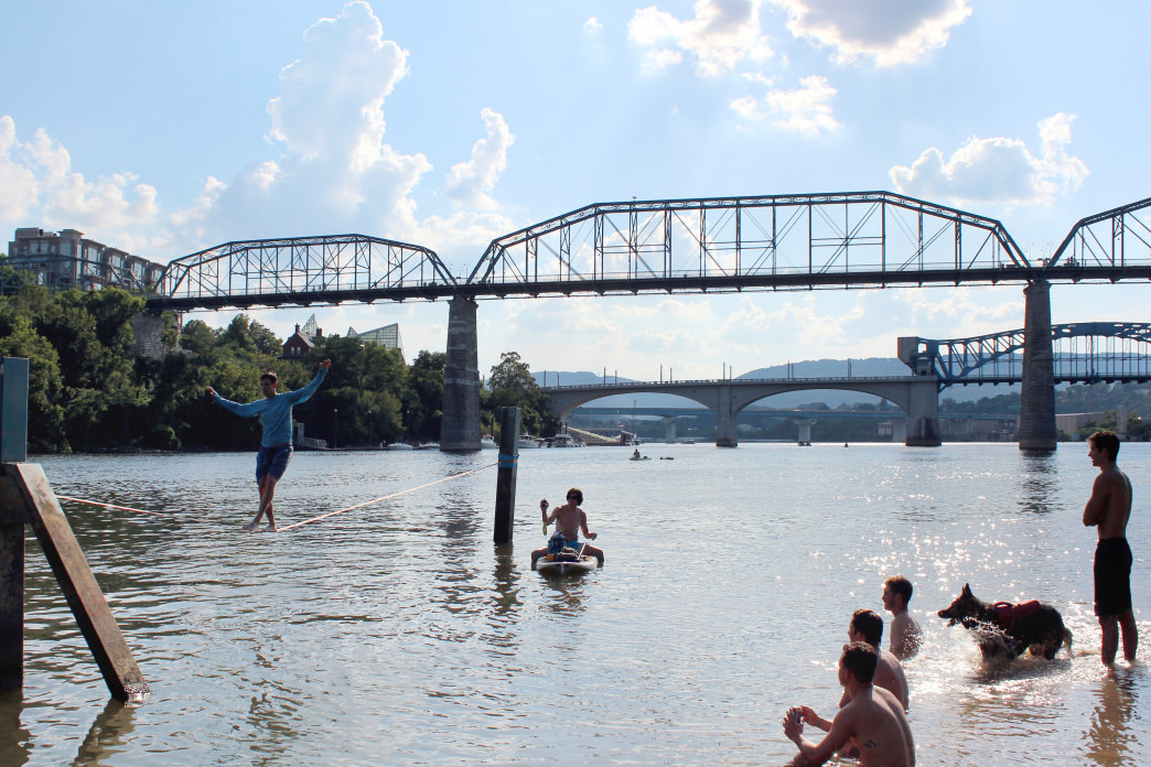 Slack-liners and paddlers in the shadow of the Walnut Street pedestrian bridge. Evan Castellano