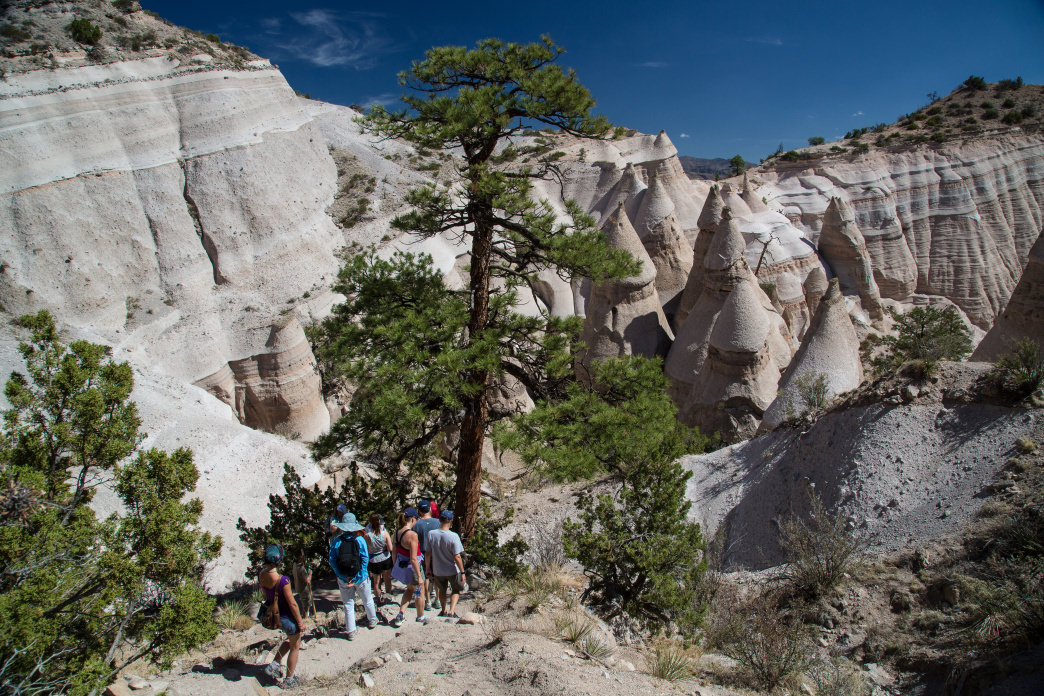 Group hiking through New Mexico's Kasha-Katuwe Tent Rocks National Monument.