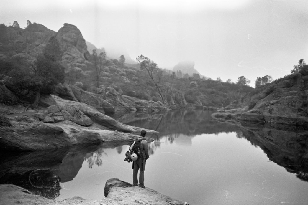 A climber contemplates a quiet pond at Pinnacles National Park.