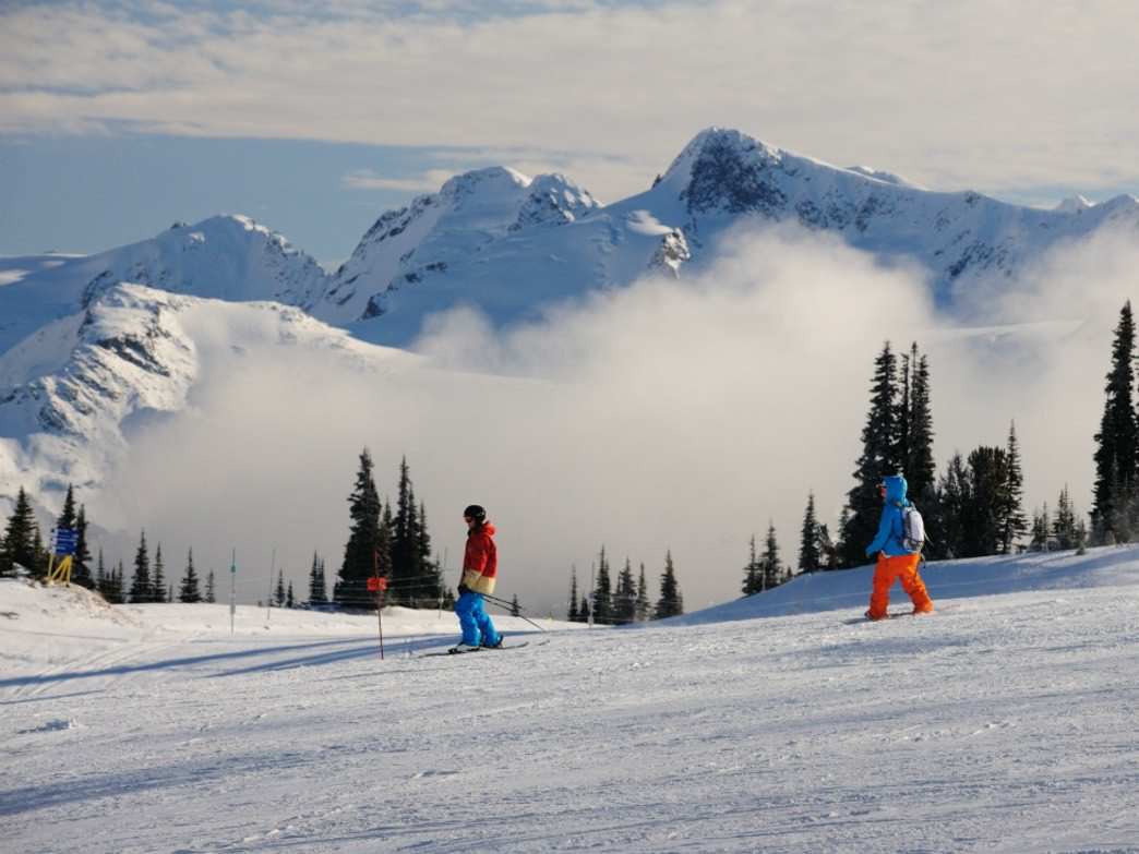 A skier and a boader cruise down a wide-open run on Whistler Mountain.