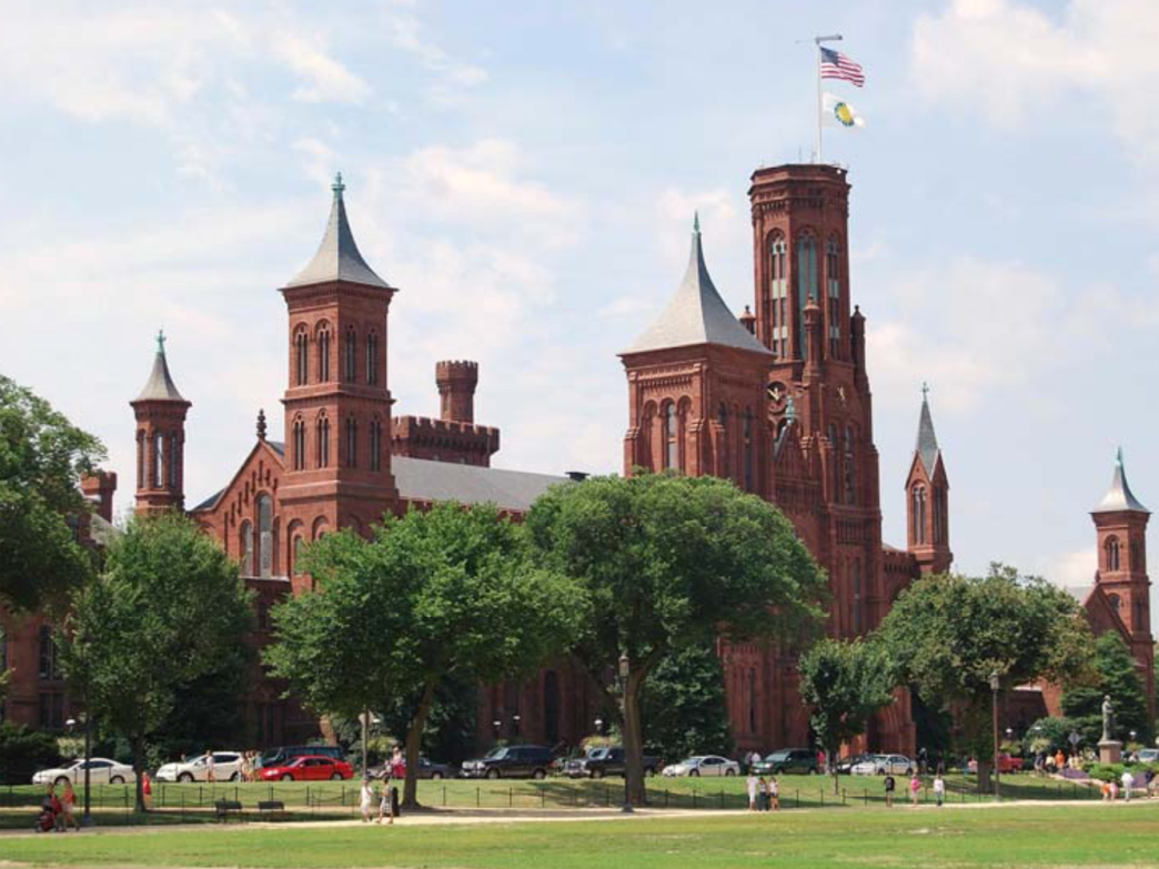The Smithsonian Castle stands behind trees along the National Mall