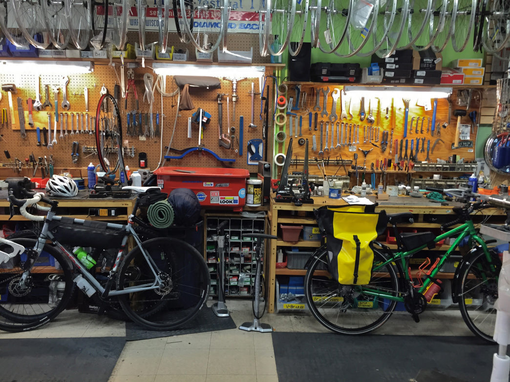 Two examples of bikepacking rigs surrounded by tools from a bike shop.
