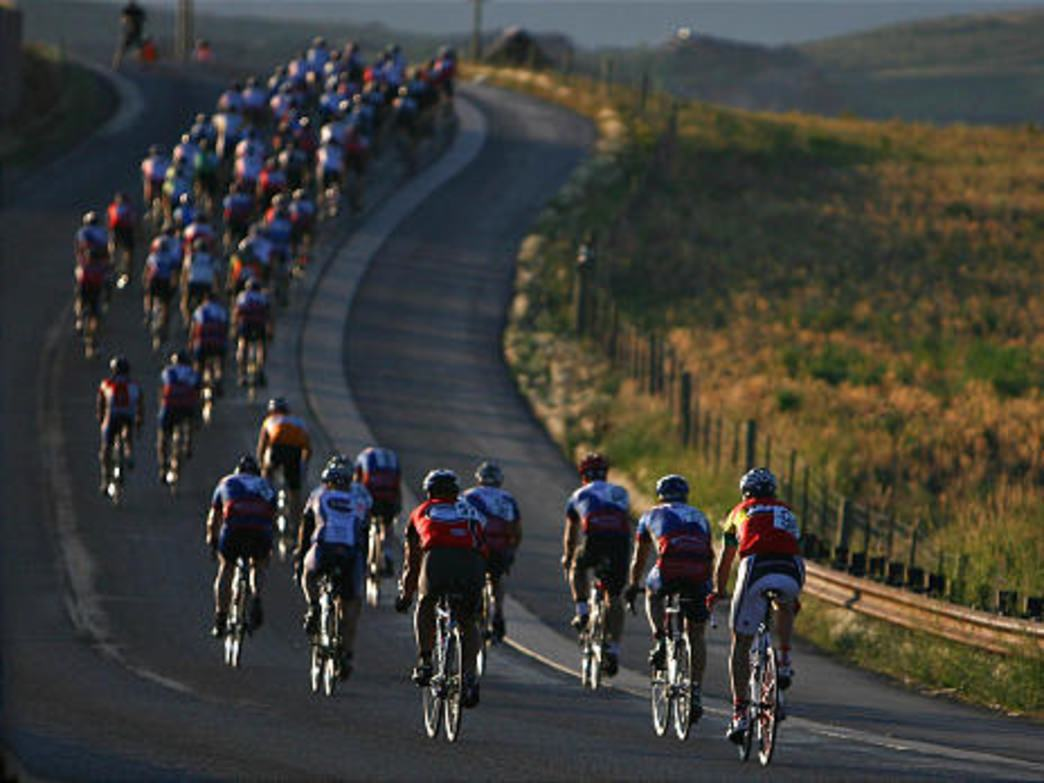 Cyclists ride through the early morning light during the Tour de Park City