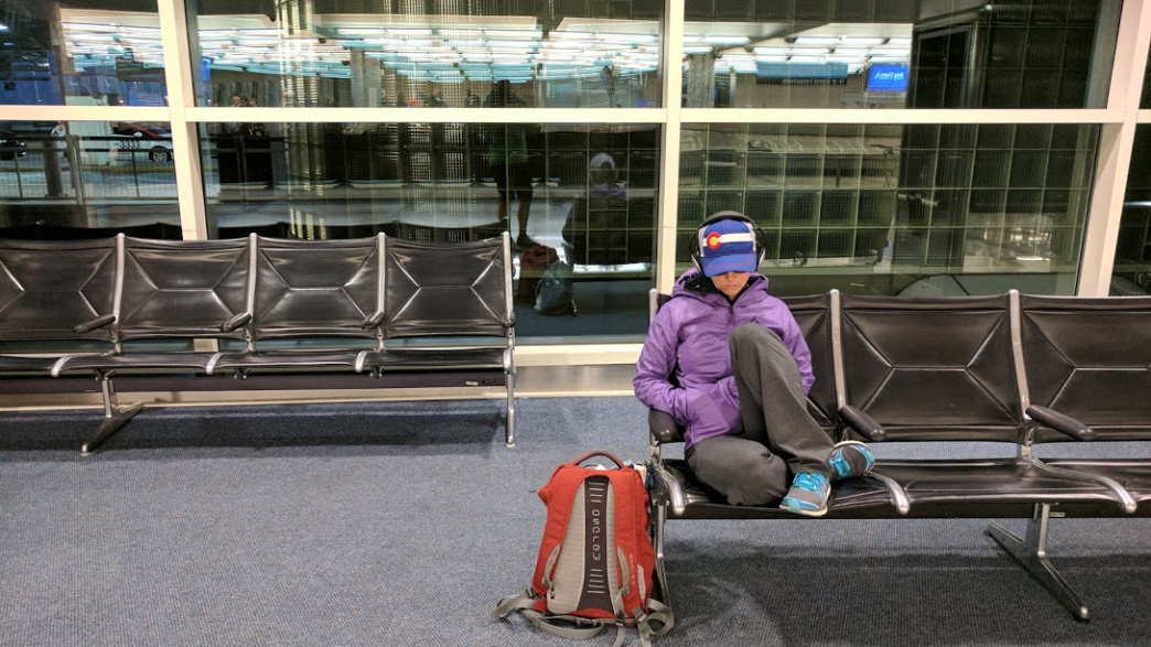 Kristin gathers herself at Denver International Airport wearing noise canceling headphones in order to lessen the auditory input.