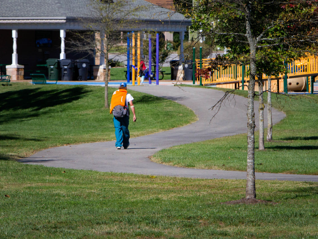 A man walks along the greenway trail through Caswell Park in East Knoxville.