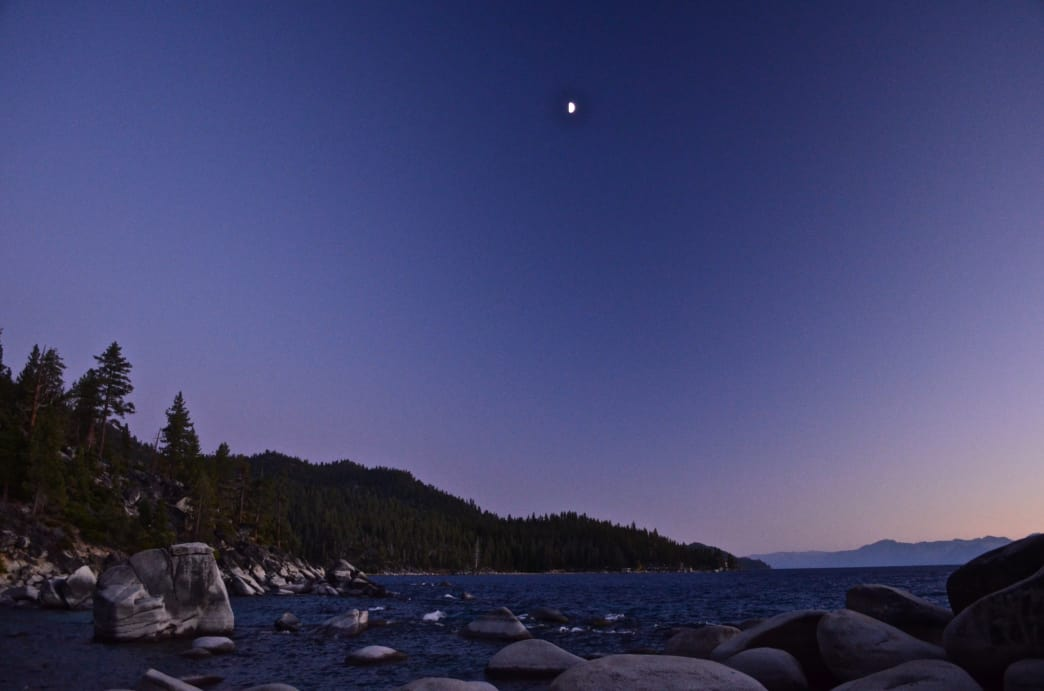 Sunset and moonrise on Tahoe's shoreline during an evening paddle adventure around the lake. Aaron Hussmann