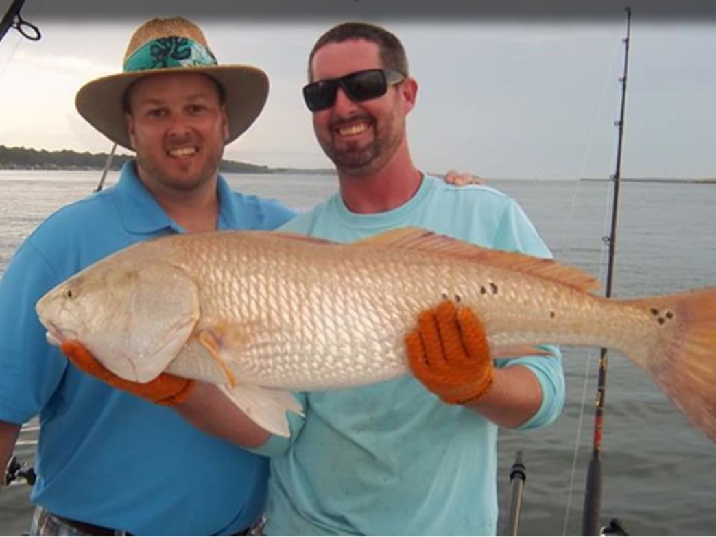 Happy fishermen with a big bull red.