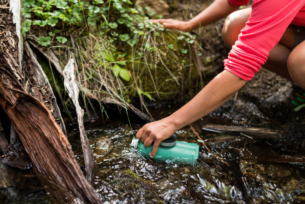 Refilling directly from a mountain stream.