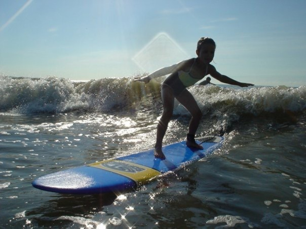 A young surfer catches one of her first waves