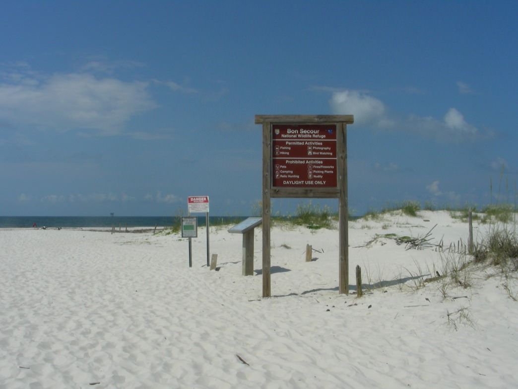 A welcoming sign posted by the US Fish and Wildlife Service reminds visitors about the rules for visiting the beach at Fort Morgan.