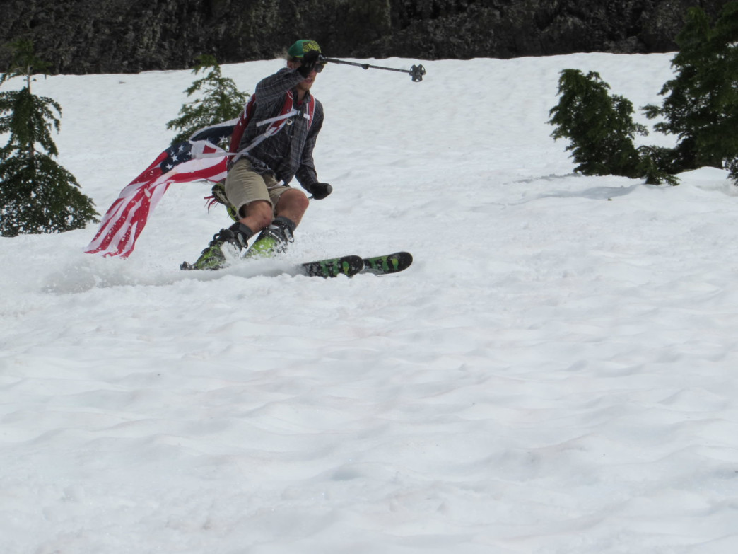 Brian Bates skiing down the slushy snow beneath the pass, flying the flag for the Fourth