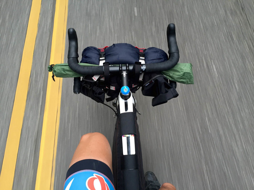 Tent poles and sleeping bag strapped to road-style handlebars.