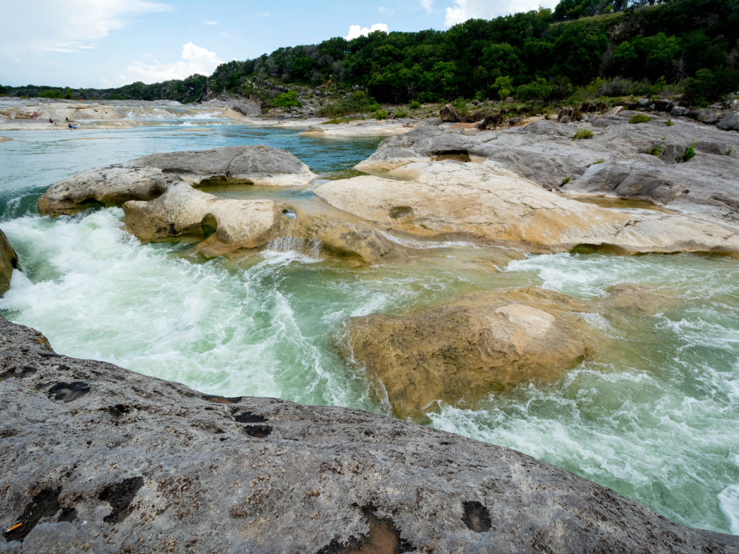 Enjoy white sandy beaches, giant boulders, and rock formations at Pedernales Falls State Park.