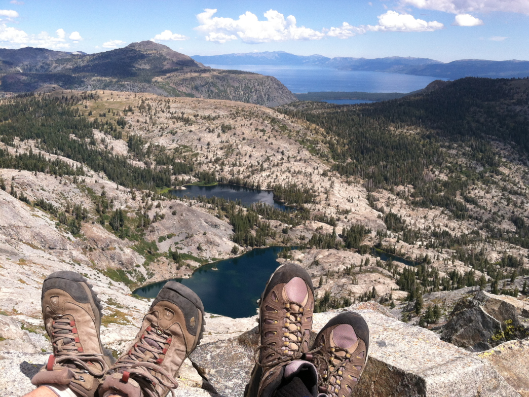 Two hikers overlook Ralston, Tamarack, and Cagwin Lakes with Lake Tahoe in the distance.