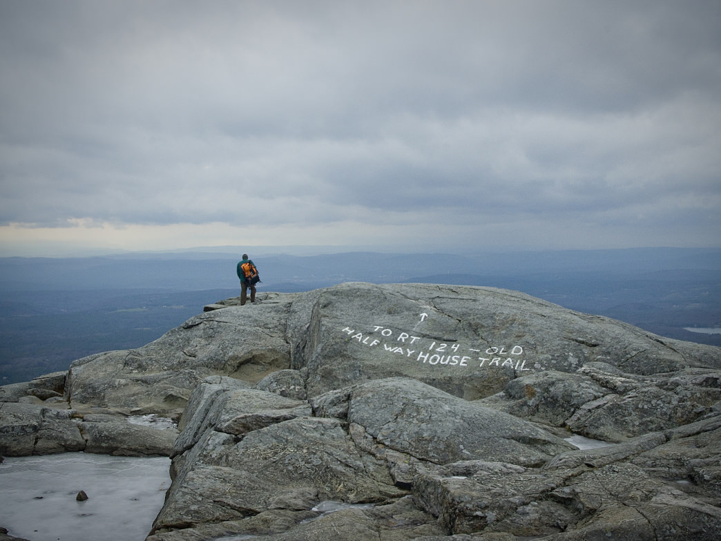 A solo hiker atop the summit of Monadnock in winter.