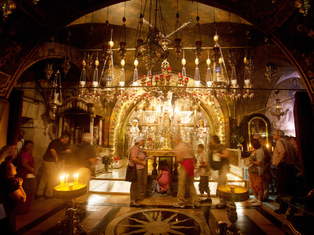 People wait their turn take to say prayers through the window that frames the Rock of the Calvary—the site where Jesus' cross was raised—at the Church of the Holy Sepulchre in Jerusalem.