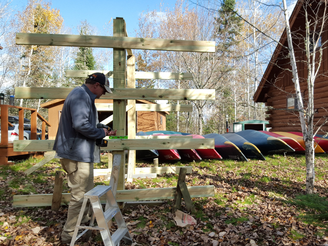 Jeff Weidman puts the finishing touches on the canoe racks in front of the cabin