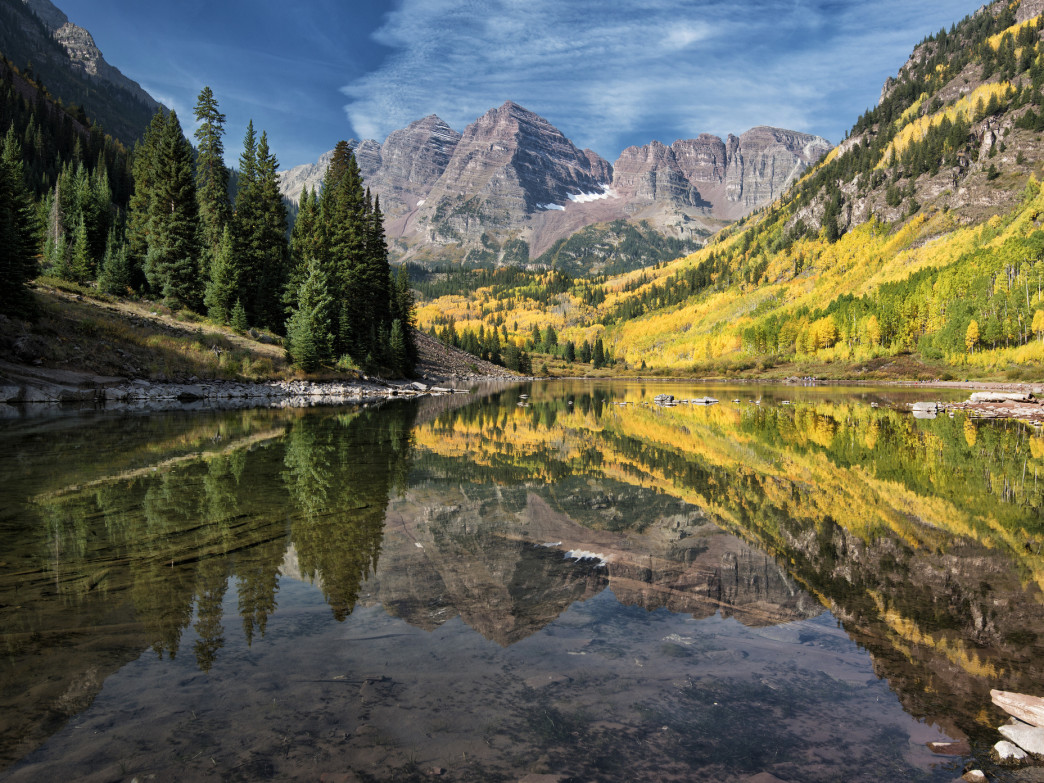 The reflection of brilliant aspen in an alpine lake makes for a jaw-dropping view.