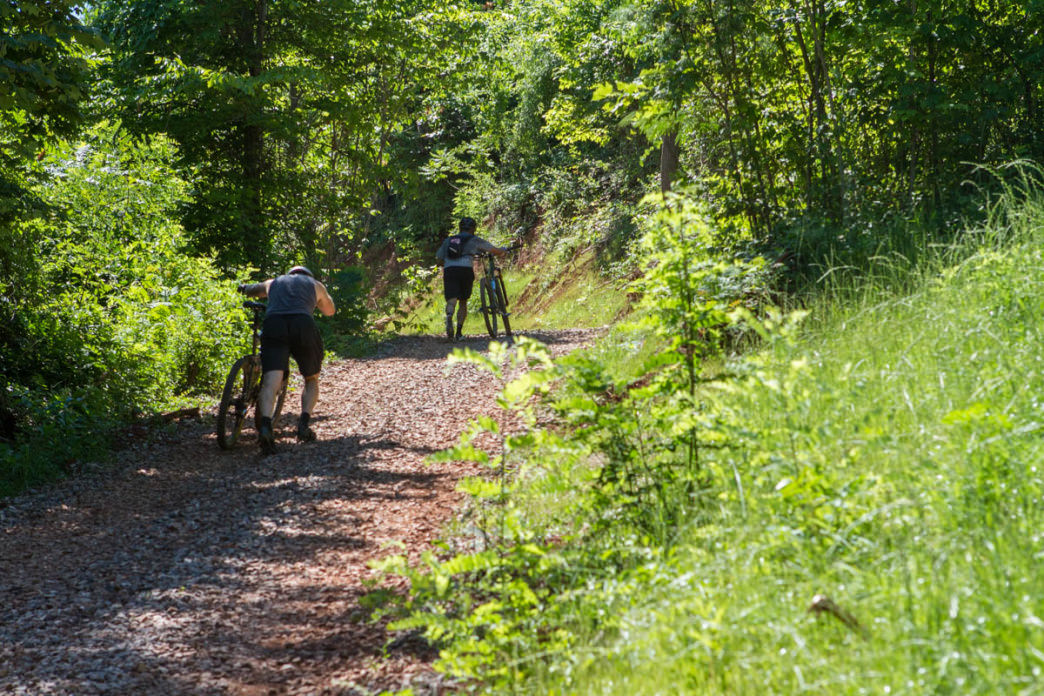 Mountain bikers trek up Pappy's Way towards the start of Devil's Racetrack at Baker Creek Preserve in Knoxville.     Clay Duda