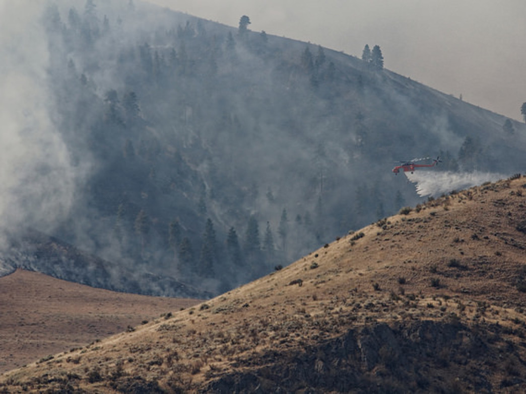 A helicopter weaves through the smoke caused by the Chelan Butte Fire.