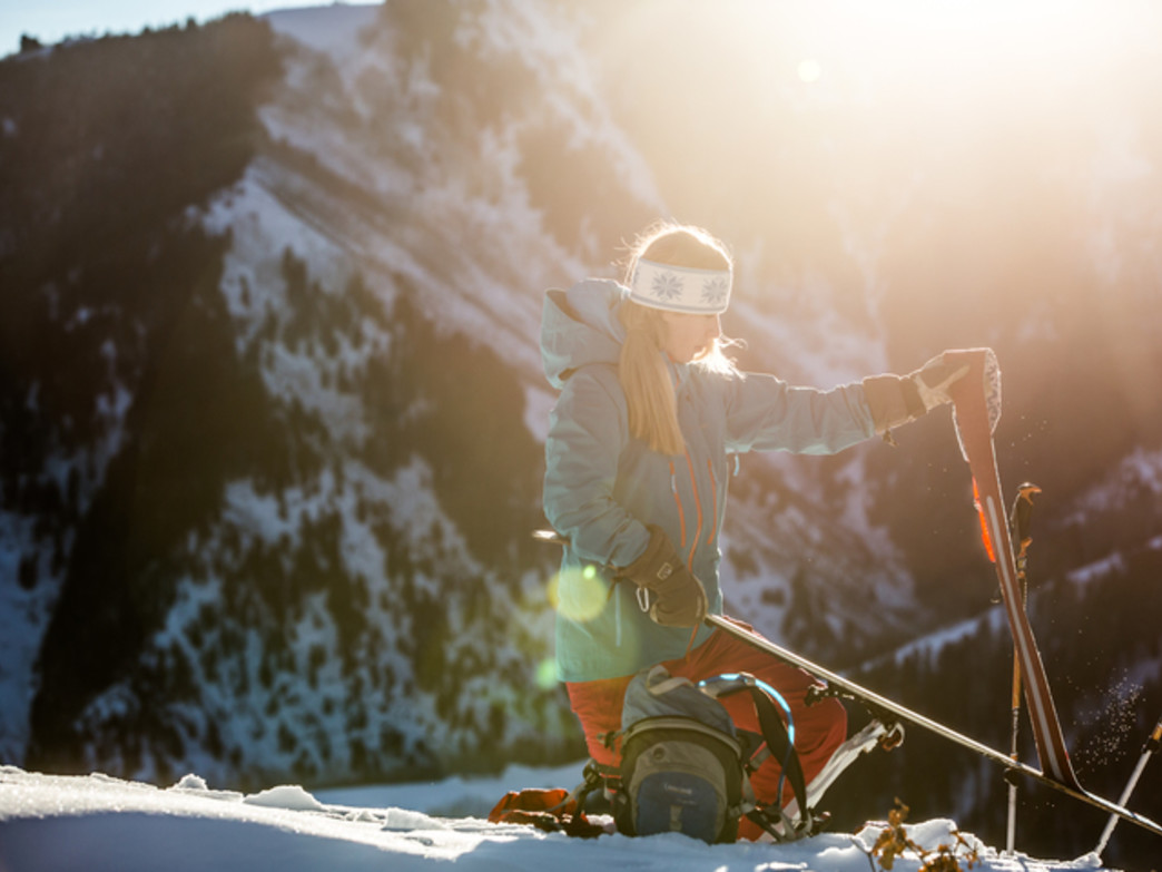 A skier removing skins from her skis after the hike up Tiehack.