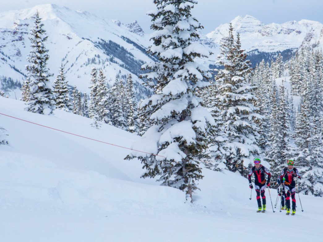 Racers heading uphill on a snowy morning at Aspen Snowmass