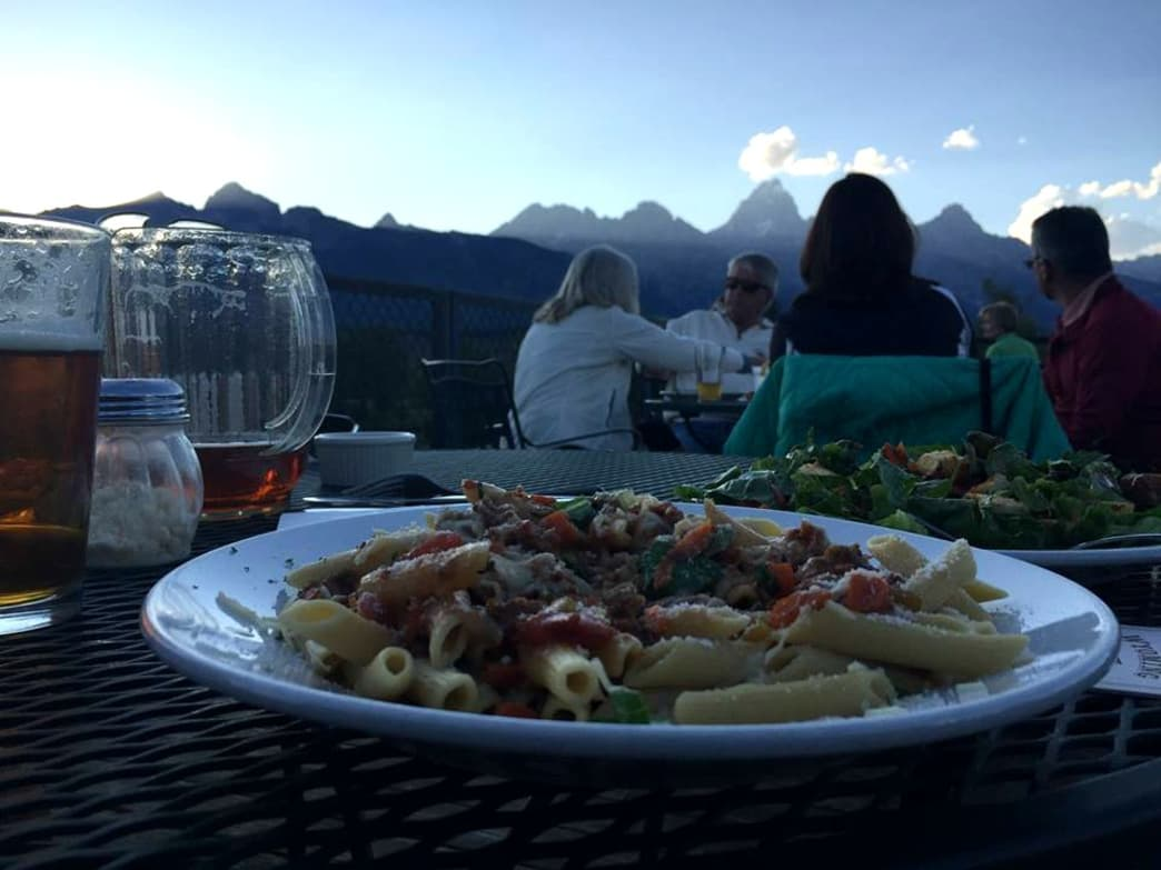 Enjoying a plate of Buffalo bolognese at Dornan's Restaurant with the Tetons looming in the background.