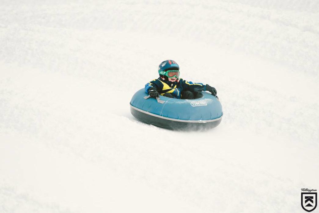 A young shredder bombing down in a tube at Killington Resort