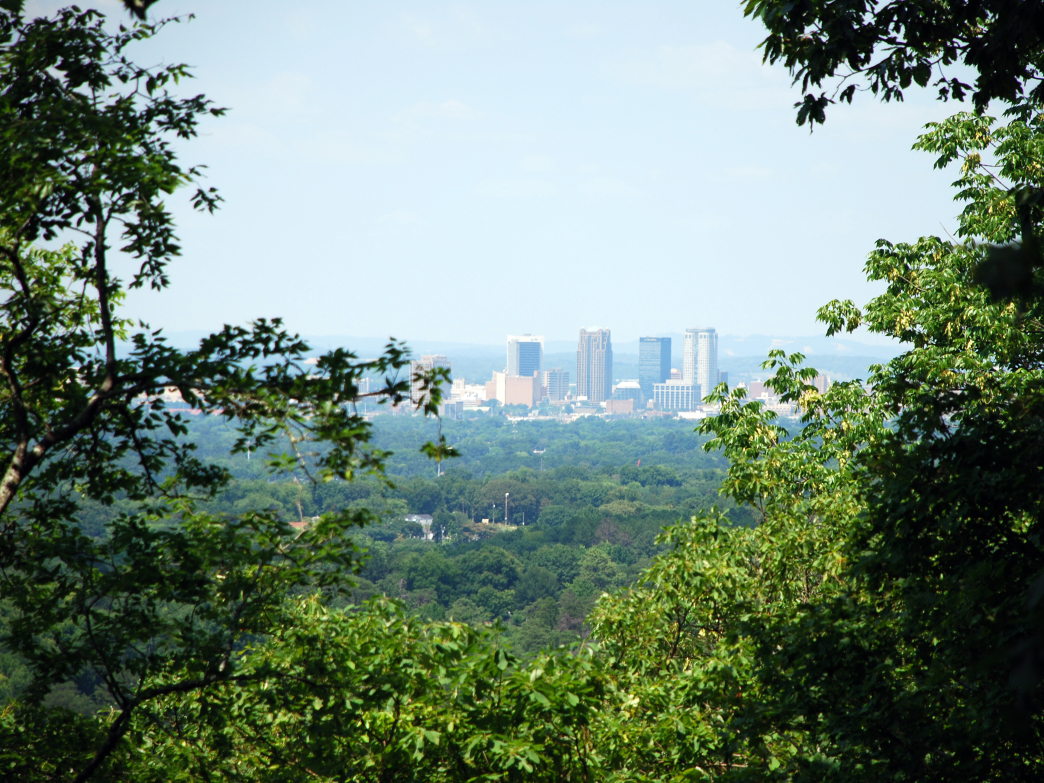 Magic City's buildings in the distance spearing into a clear blue sky, witnessed from Red Mountain Park.