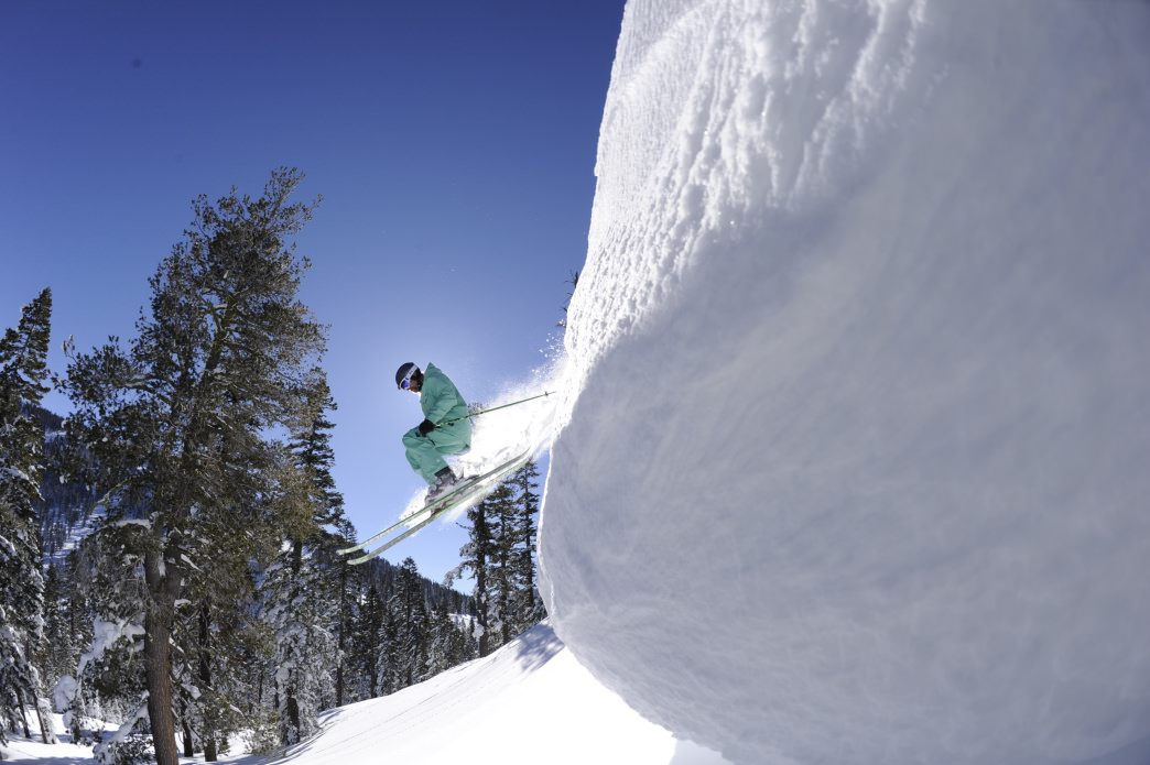 A skier bombs off a cliff on a pow day at Northstar.
