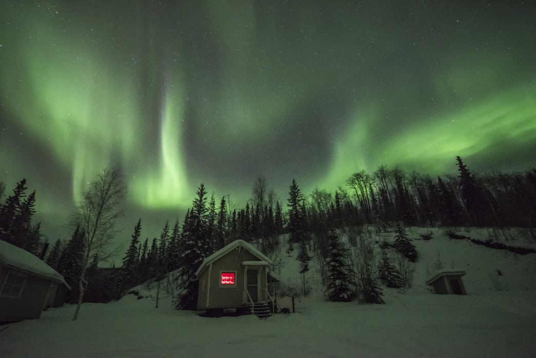 An Aurora dances and shimmers overhead above a cabin at Coal Creek Camp within Yukon-Charley Rivers National Preserve.