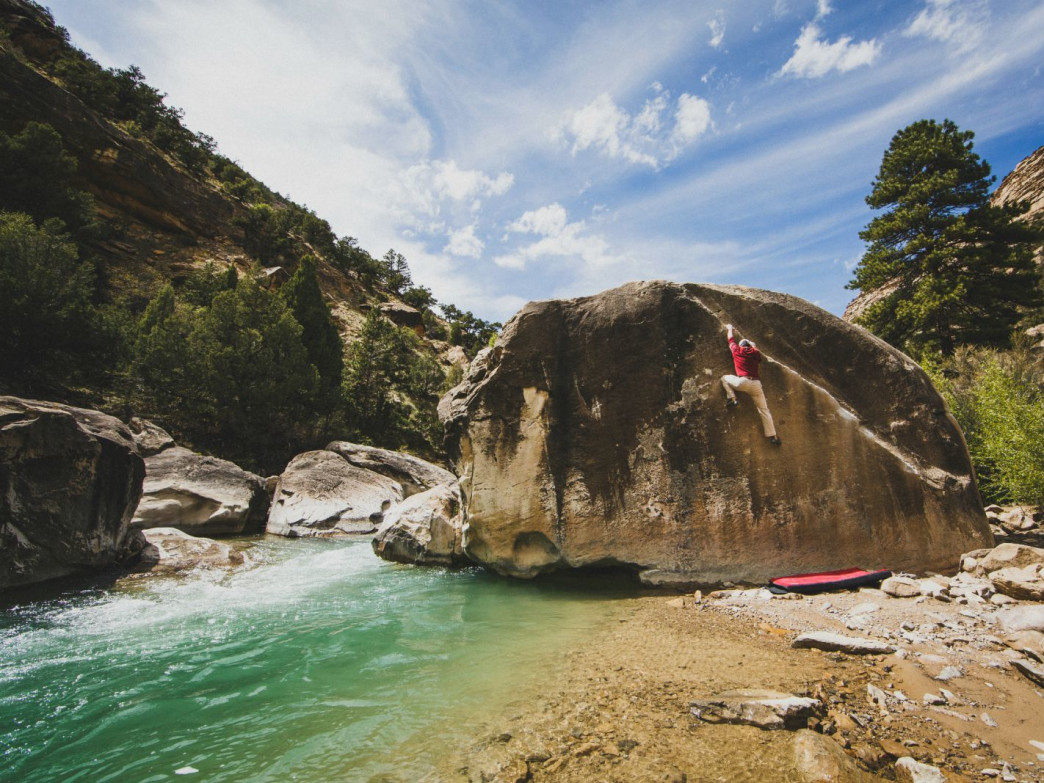 Climbing a boulder above the emerald waters of Cottonwood Creek in Joe's Valley