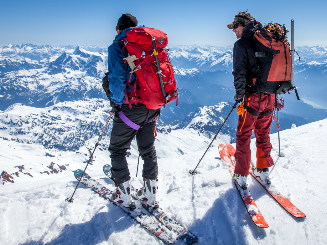 Just below the summit of Mount Baker, Benj Wadsworth and Adam Justin look northwest into the rugged North Cascades.