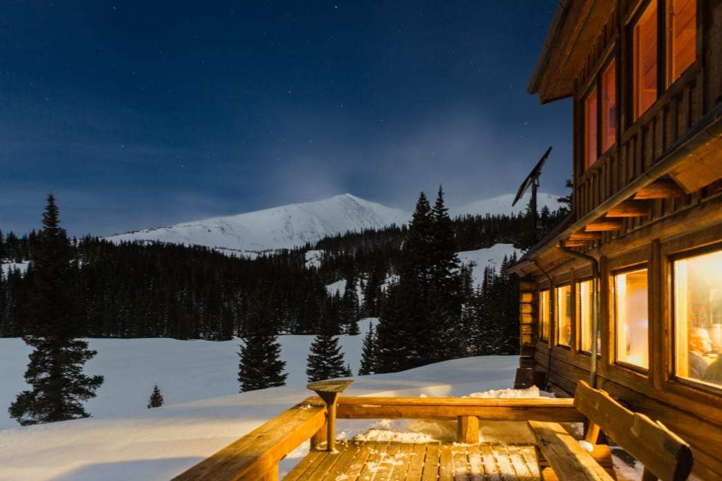 The 10th Mountain Hut casts a warm, inviting glow as night falls.