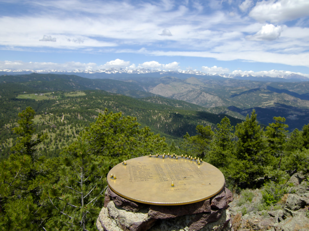The summit marker on Green Mountain identifies distant peaks.