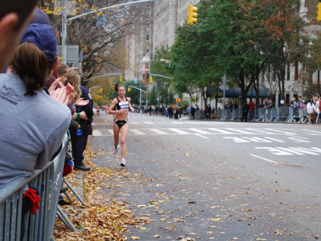Spectators cheering for an elite female runner at the NYC Marathon