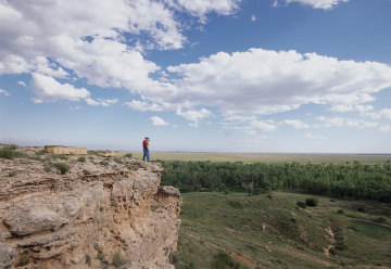 Man on cliff looking out over the Cimarron Grasslands