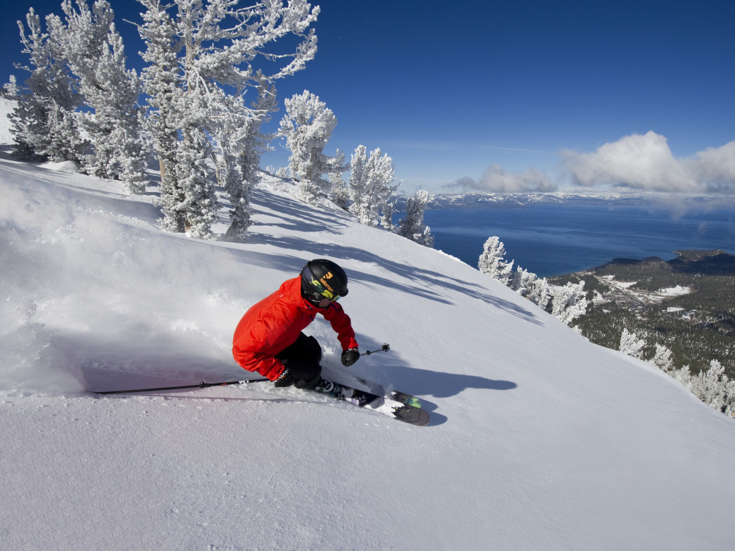 A skier rips through fresh powder at Heavenly, with epic views of Lake Tahoe.