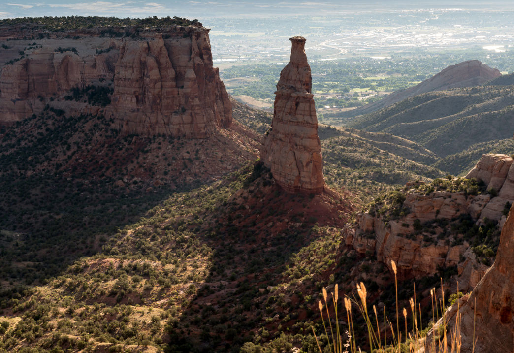 Independence Rock is a towering pillar standing all alone amid the surrounding red and green canyon backdrop.