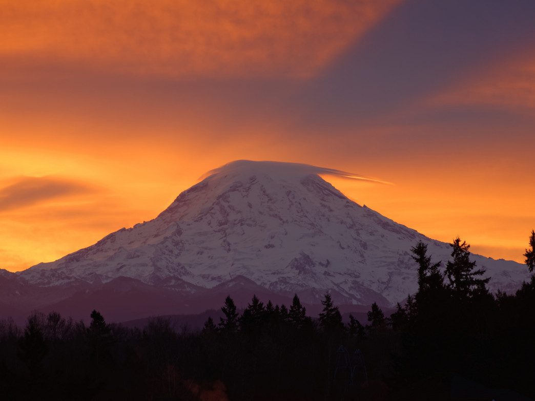 The sunrise swelling behind Mt. Rainier.