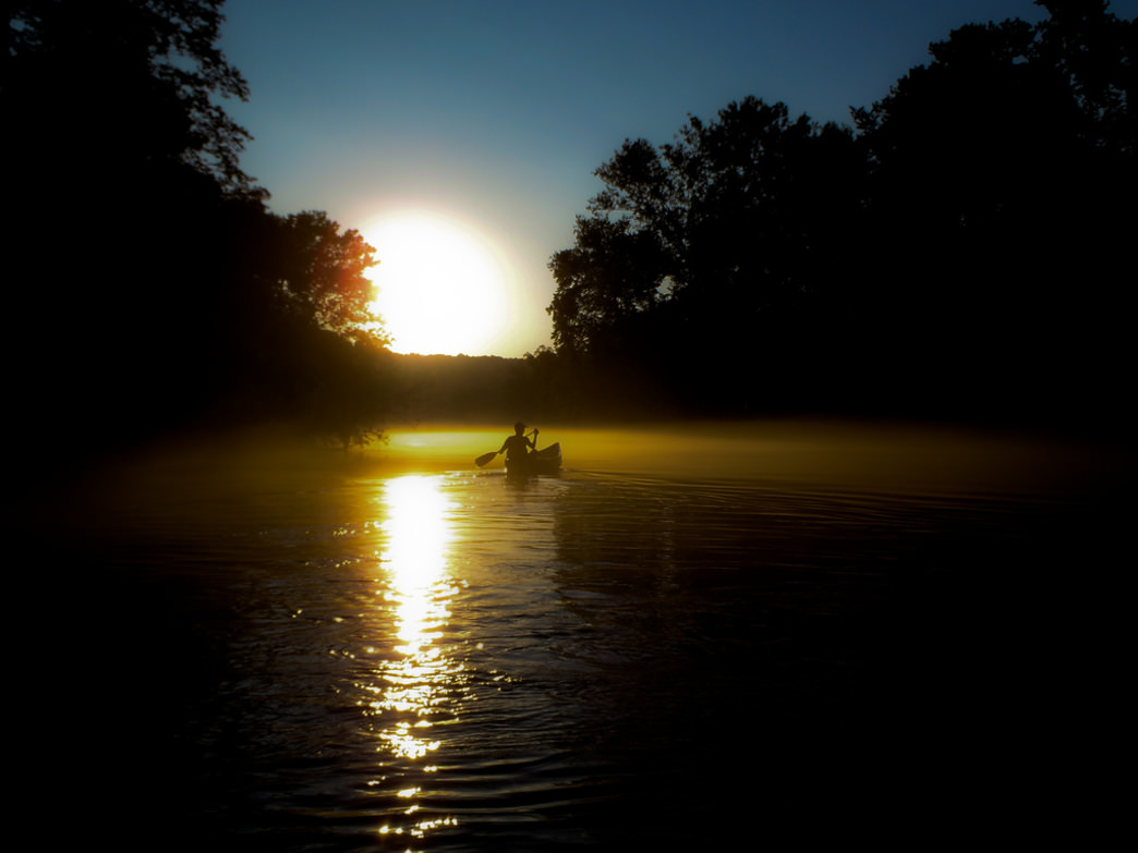 A canoeist paddling  the Missouri River at sunset.