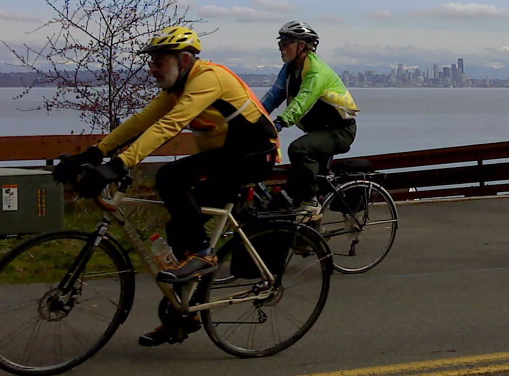 Cyclists race past a scenic view of the Seattle skyline from Bainbridge Island.